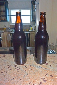 Two bottles of Backyard Homebrew, open and ready to pour.